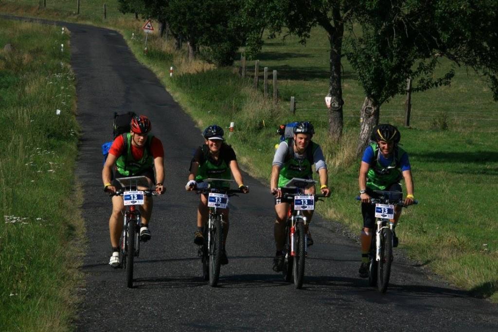 Zawodnicy z ogromnymi i ciężkimi plecakami jadą na rowerach.